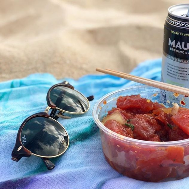 A photograph of Ray Ban sunglasses and a bowl of poke at the beach.