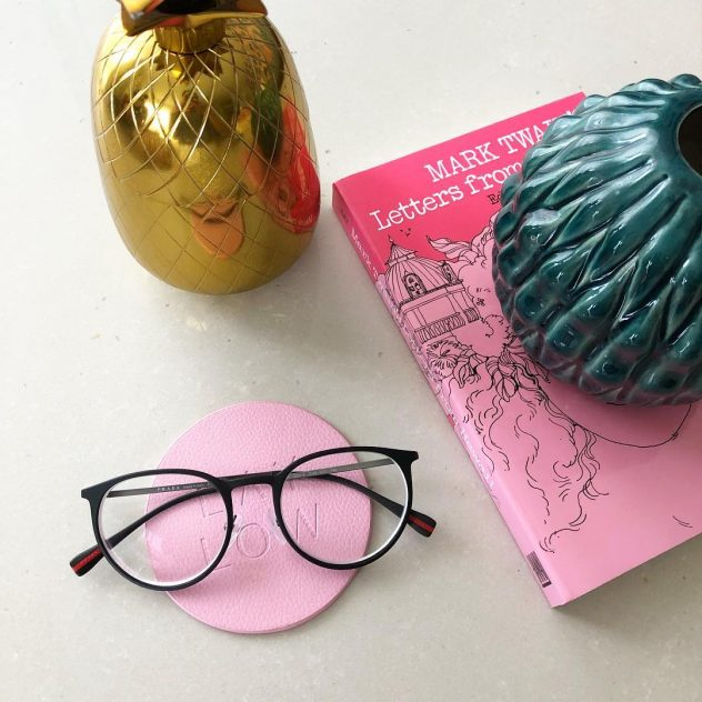 Photo graph of eyeglasses and a book.