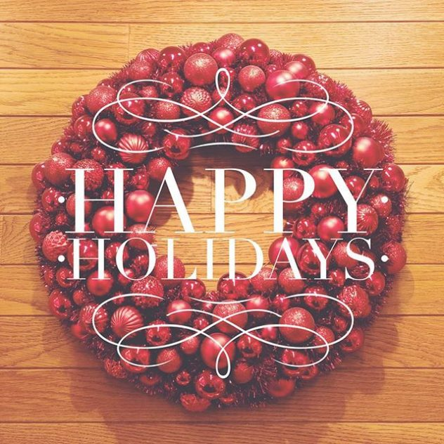 """Photo of a Christmas wreath with the words """"Happy Holidays"""" overlayed"""