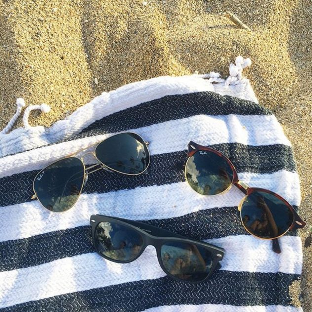 Three Ray Ban sunglasses on a towel at the beach.
